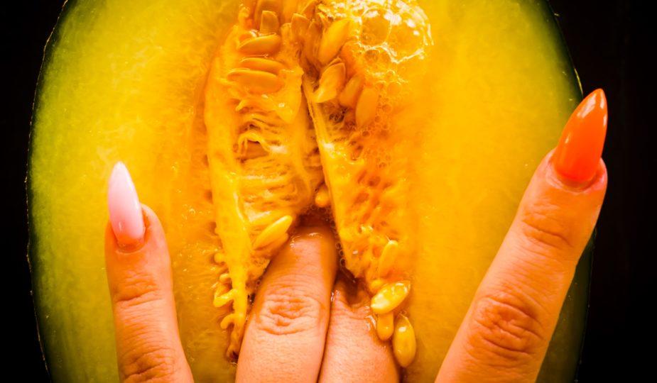 doigts dans un fruit qui fait penser à une vulve