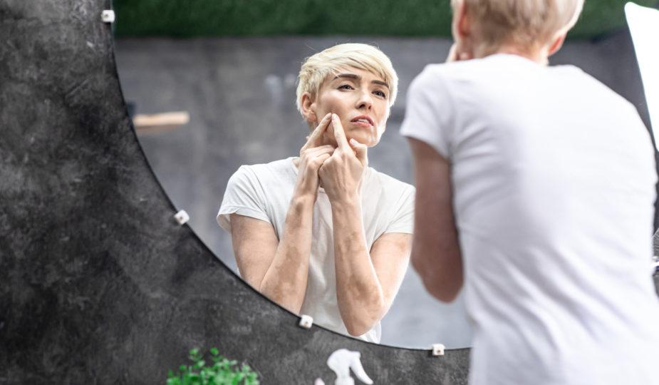 l'acné après 50 ans, que faire. Femme devant miroir se perce un bouton